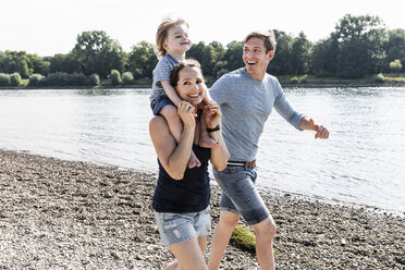 Happy family walking at the riverside on a beautiful summer day - UUF15015