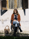 Portrait of smiling woman sitting in front of house enjoying sunlight - RAMAF00053