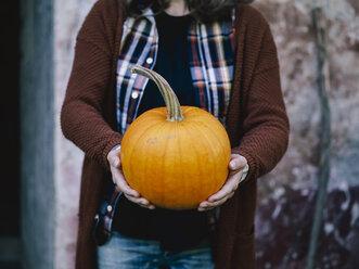 Woman's hands holding big pumpkin - RAMAF00062