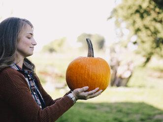 Proud woman holding big pumpkin - RAMAF00065