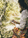 Italy, woman leaning against olive tree using cell phone - RAMAF00071