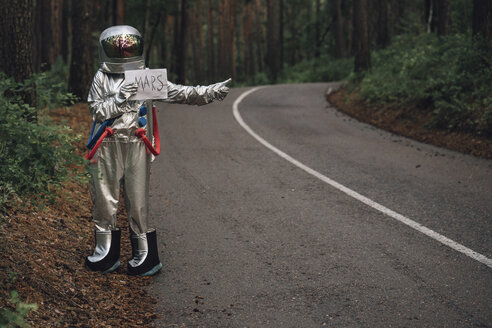 Spaceman hitchhiking to Mars, standing on road in forest - VPIF00554