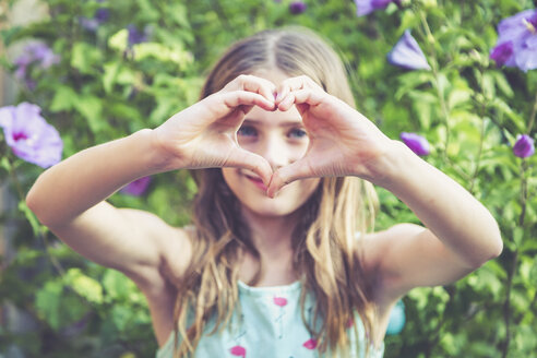 Young girl making a heart shape with her fingers - SARF03932
