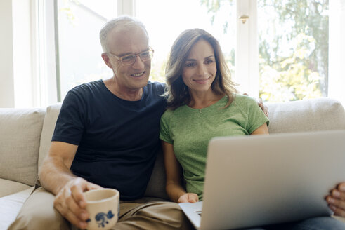 Smiling mature couple sitting on couch at home sharing laptop - KNSF04597