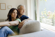 Smiling mature couple sitting on couch at home looking out of window - KNSF04600