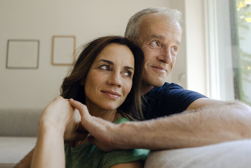 Smiling mature couple sitting on couch at home - KNSF04603