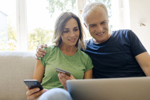 Smiling mature couple sitting on couch at home shopping online with laptop and smartphone - KNSF04609