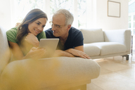 Smiling mature couple lying on couch at home sharing tablet - KNSF04615