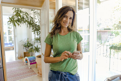 Portrait of smiling mature woman using cell phone at home - KNSF04618