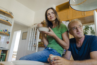 Confident mature couple at home looking sideways - KNSF04621