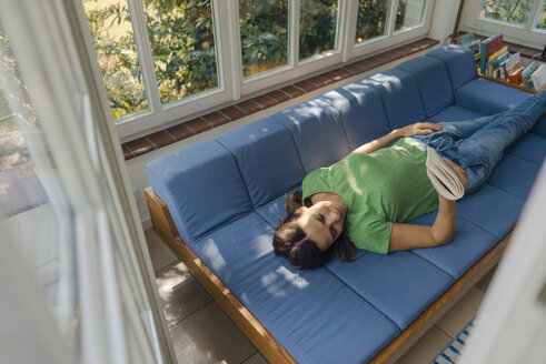 Mature woman lying on couch at home reading book - KNSF04627