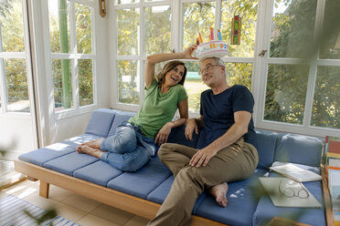 Playful mature couple sitting on couch at home with fake birthday cake - KNSF04636