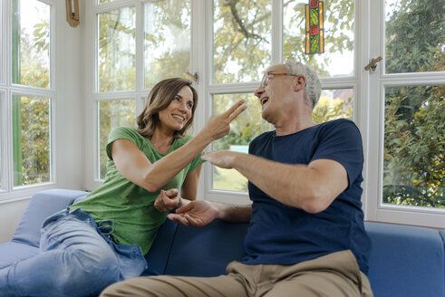 Happy mature couple sitting on couch at home playing Scissors Paper Stone - KNSF04639