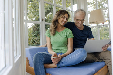 Smiling mature couple sitting on couch at home sharing laptop - KNSF04642