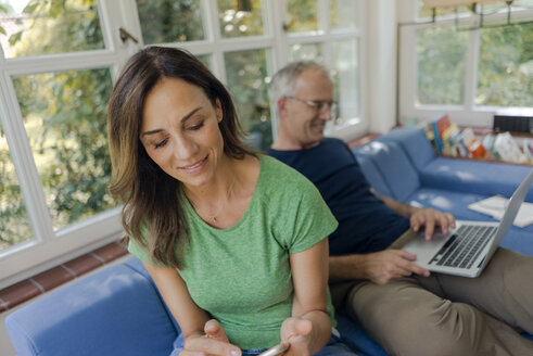 Mature couple sitting on couch at home with woman using cell phone and man using laptop - KNSF04645