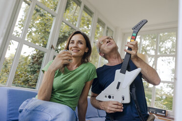Mature couple sitting on couch at home with man playing toy electric guitar - KNSF04648