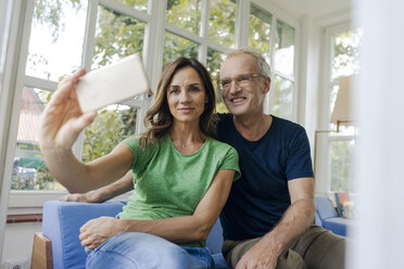 Smiling mature couple taking a selfie at home - KNSF04651