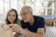Mature couple lying on the floor at home looking at globe - KNSF04654