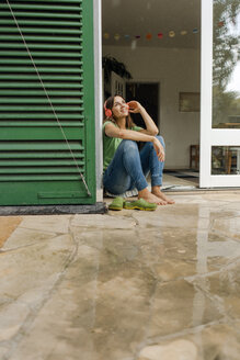 Smiling mature woman sitting on wet terrace listening to music with headphones - KNSF04663