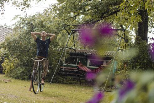 Mature man with bicycle enjoying summer rain in garden - KNSF04669
