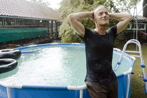 Mature man enjoying summer rain in garden at swimming pool - KNSF04675