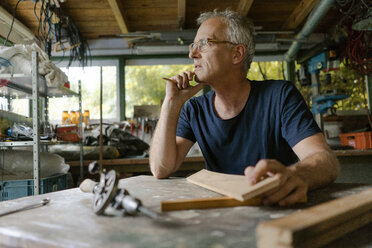 Mature man at workbench in his workshop thinking - KNSF04693