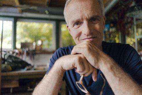 Portrait of confident mature man in his workshop - KNSF04696