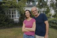 Happy mature couple standing in garden of their home - KNSF04702