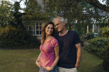 Smiling mature couple standing in garden of their home - KNSF04705