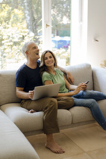 Happy mature couple sitting on couch at home with cell phone and laptop - KNSF04708