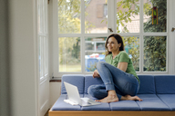 Smiling mature woman sitting on couch at home with laptop - KNSF04717