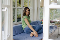 Smiling mature woman sitting on couch at home - KNSF04720