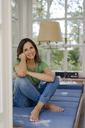 Smiling mature woman sitting on couch at home - KNSF04726