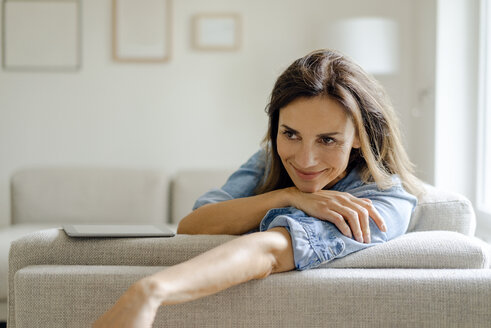 Portrait of smiling mature woman resting on couch at home - KNSF04732