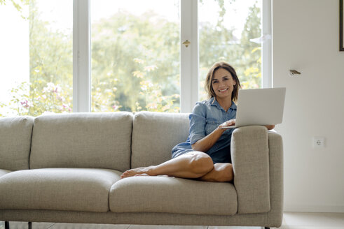 Smiling mature woman sitting on couch at home with laptop - KNSF04735