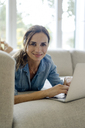 Portrait of smiling mature woman lying on couch at home using laptop - KNSF04738