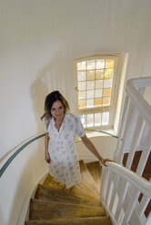 Smiling mature woman walking up spiral staircase - KNSF04750