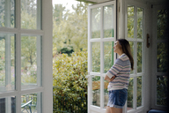 Mature woman looking out of terrace door at home - KNSF04768