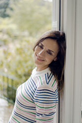 Portrait of smiling mature woman leaning against terrace door at home - KNSF04771