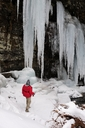 A man looking up at large icicles while trying to fly fish. - AURF02683