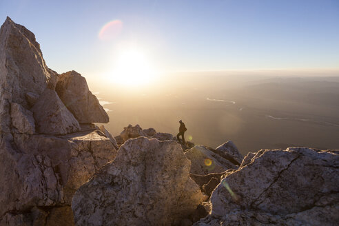 A climber watches the sunrise from below the summit of Teewinot Mountain, Grand Teton National Park, Wyoming. - AURF02932