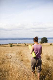 A young woman, wearing a purple shirt, carries a green yoga mat through a field of golden grasses overlooking the ocean. - AURF02935
