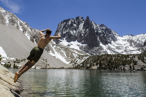 Cannonball time, a young man jumps in a desolation lake in the John Muir Wilderness, Eastern Sierras, California. - AURF03046