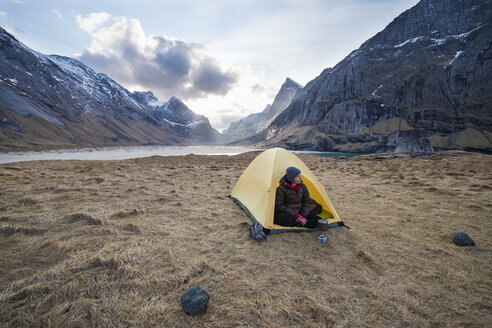 Female backpacker takes in view from tent while camping at Horseid beach, Moskenes├©y, Lofoten Islands, Norway - AURF03112