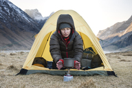 Female hiker warms hands with stove on cold morning wild camping at Horseid beach, Moskenes├©y, Lofoten Islands, Norway - AURF03115