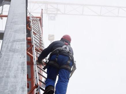 Germany, Bavaria, Garmisch-Partenkirchen, Zugspitze, installer climbing ladder on pole at goods cable lift - CVF01072