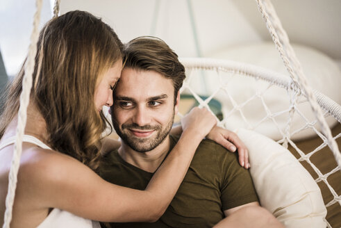Happy affectionate couple embracing in hanging chair at home - JOSF02550
