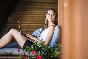 Smiling woman on balcony using laptop - JOSF02577