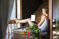 Woman relaxing on balcony using laptop - JOSF02580