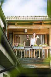 Smiling couple standing on balcony at home - JOSF02592